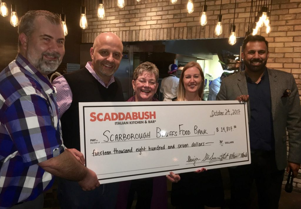 Representatives from The Bluffs Food Bank accept a donation from Scaddabush Italian Kitchen & Bar at the Scarborough Town Centre