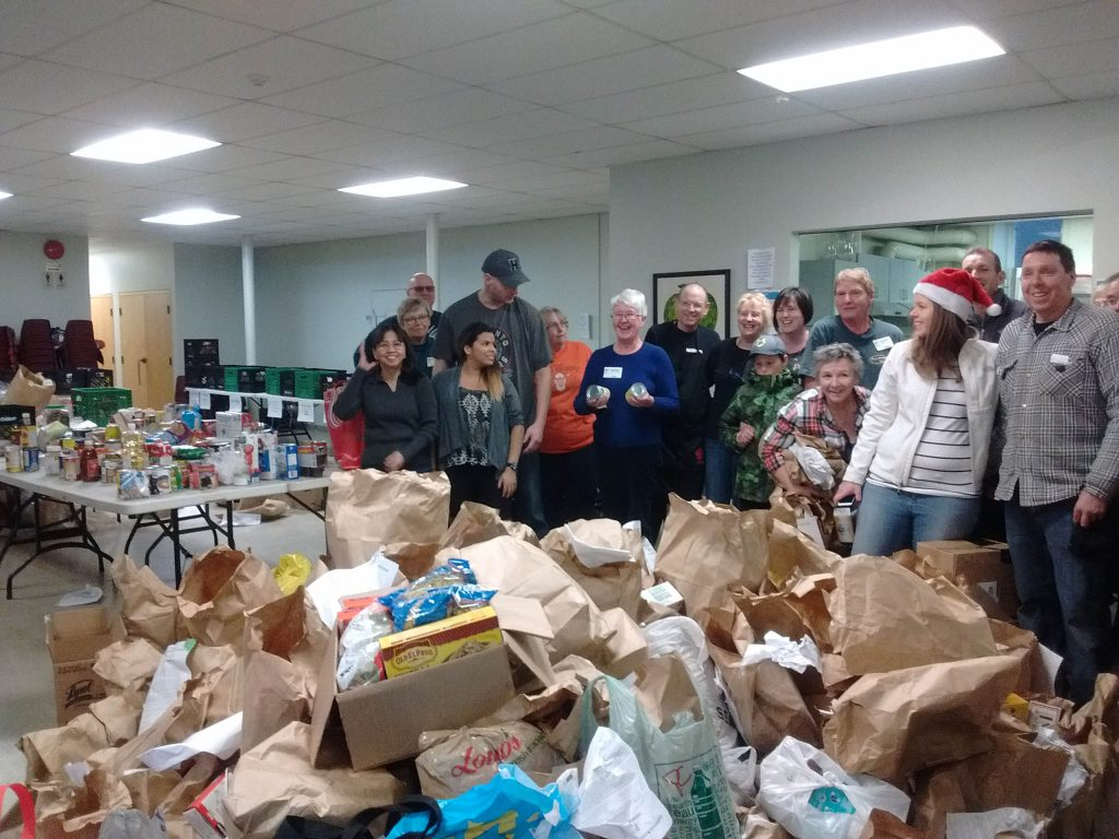 Volunteers from the community and regular Bluffs Food Bank volunteers sort through several hundred pounds of food donations.